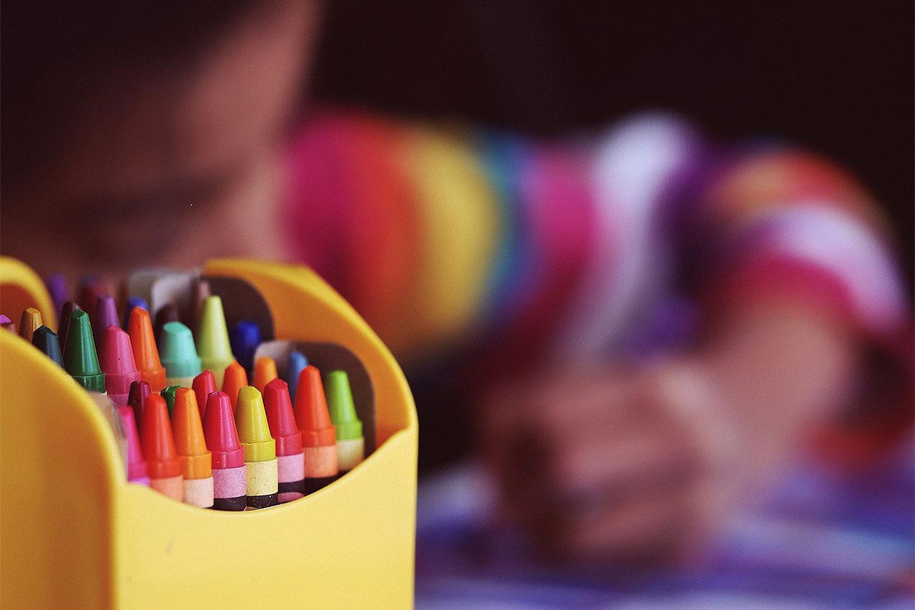 Criança colorindo com lápis de cera