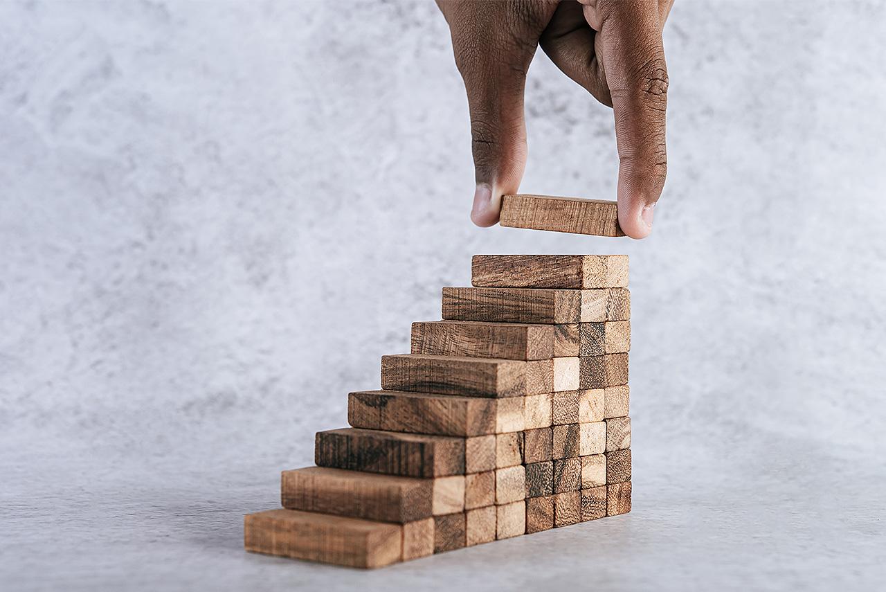 Mão empilha peças de madeira em uma ideia de crescimento
