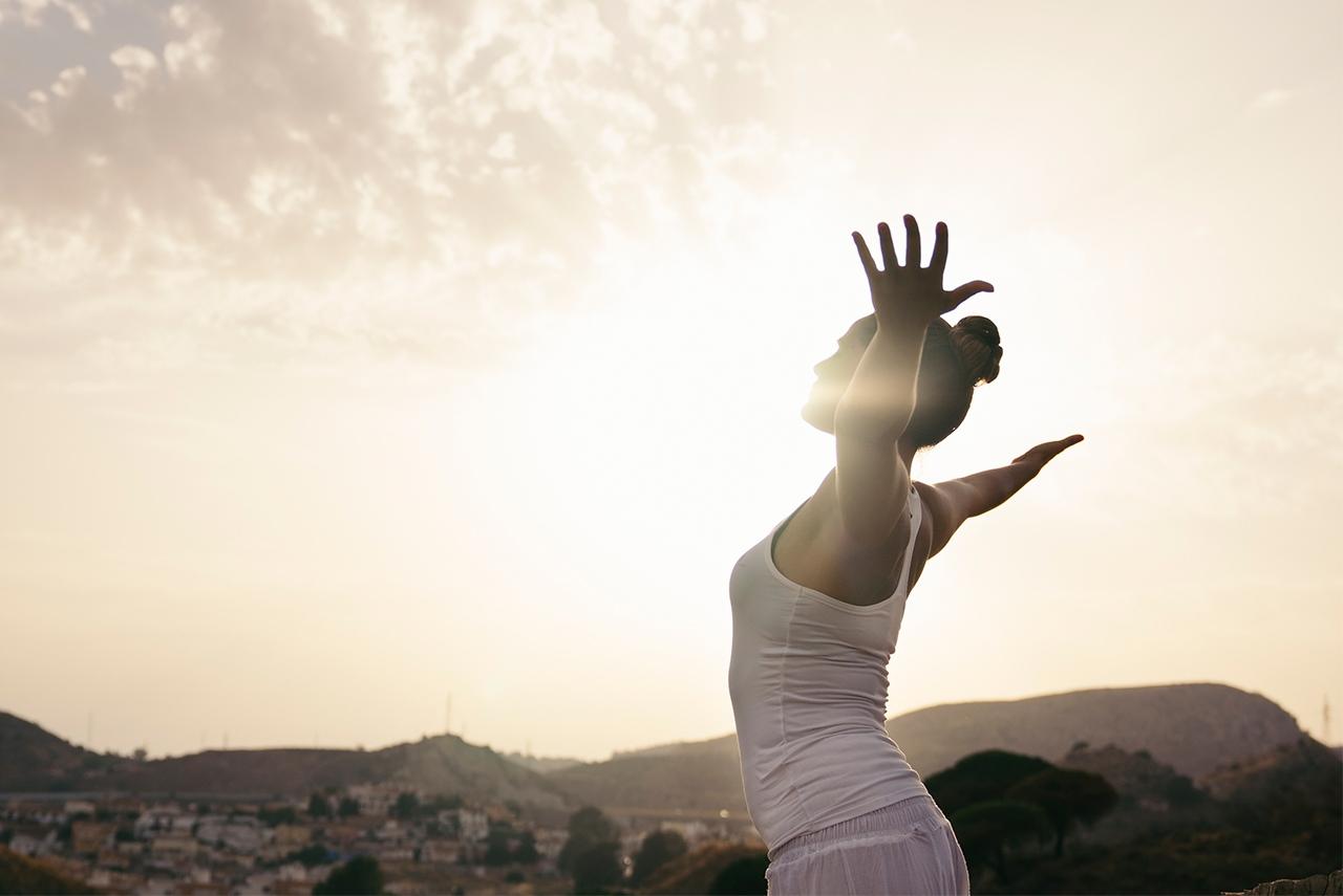 Mulher alonga o corpo enquanto olha para o horizonte