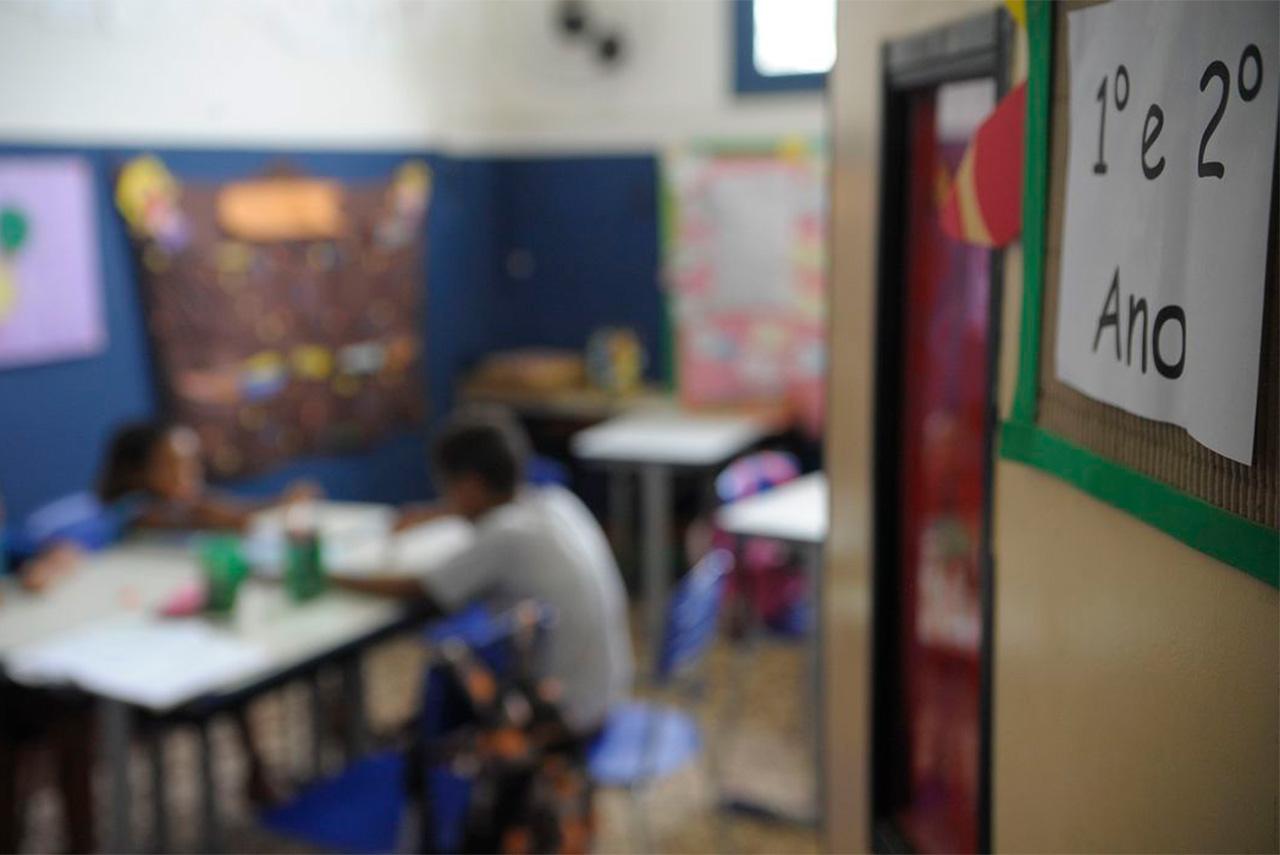 Sala de aula de ensino fundamental com crianças sentadas e desenvolvendo trabalho em grupo